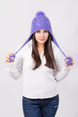 Cute young teenage girl wearing purple beanie hat caucasian brunette looking at camera posing holding pom poms winter fashion Royalty Free Stock Photography