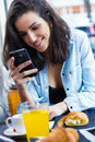 Cute young woman chatting with their smartphone at coffee shop Royalty Free Stock Image