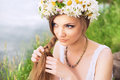 Cute young woman with circlet of camomile braiding her hair at t