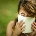 Cute young woman covering her face with a book she is reading Royalty Free Stock Images
