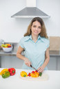 Cute young woman cutting vegetables standing in kitchen smiling at camera Royalty Free Stock Image