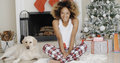 Cute young woman and her dog at christmas sitting together on the floor in front of the decorated tree with gifts smiling happily Royalty Free Stock Image