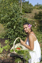 Cute young woman in her garden female gardener holding fresh picked plants beautiful organic Royalty Free Stock Photo