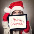 Cute young woman hiding behind tablet computer wearing santa hat happy caucasian with with merry christmas text message christmas Stock Image