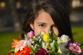 Cute young woman hiding her face behind bouquet in a park Stock Photos
