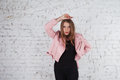 Cute young woman on leather jacket. Fashion model in pink leather jacket. Posing near white brick wall. Royalty Free Stock Photo