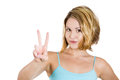 Cute young woman showing the peace victory hand sign isolated on a white background Royalty Free Stock Image