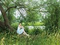 Cute young woman sitting on a beautiful, flowering tree Royalty Free Stock Photo