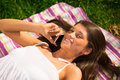 Cute young woman speaking on a mobile phone on the grass closeup portrait of Royalty Free Stock Images