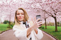 Cute young woman at spring blossom park taking self portrait gesturing peace sign while her picture with mobile phone caucasian Stock Photos