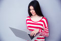 Cute young woman using laptop over gray background Royalty Free Stock Photo