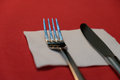 Cutlery iron on a red table fork and knife Royalty Free Stock Photography