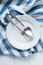 Cutlery porcelain plate and white linen napkin vintage on wooden board rustic style Royalty Free Stock Image