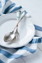 Cutlery porcelain plate and white linen napkin vintage on wooden board rustic style Royalty Free Stock Images