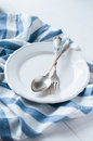 Cutlery porcelain plate and white linen napkin vintage on wooden board rustic style Royalty Free Stock Photos
