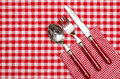 Cutlery with red knife fork and spoon on checked napkin table cloth Stock Image