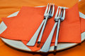 Cutlery on red napkin on white plate on arange table cloth Stock Photo