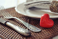 Cutlery and red stone heart white plate fork knife on wicker wooden background closeup selective focus Royalty Free Stock Photos
