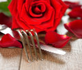 Cutlery and rose on a brown table Royalty Free Stock Images