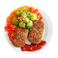 Cutlets with vegetables over white background Royalty Free Stock Image
