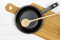 Cutting board with frying pan and wooden spoon Royalty Free Stock Photo