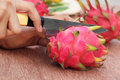 Cutting dragon fruit with a kitchen knife Royalty Free Stock Images
