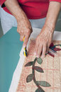 Cutting edge of quilt fabric a quilter squares up the corners a using a right angle ruler and cutter Stock Images