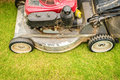 Cutting green grass in yard with lawnmower close up view of its front wheel focus or garden lawn trimming and gardening as Stock Images