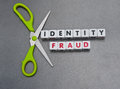 Cutting identity fraud pair scissors against text in uppercase letters inscribed on small white cubes gray background Stock Photography