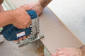 Cutting laminate with electric saw two workers carpenters a laminated floor board Stock Image