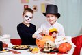 Cutting pumpkin photo of two eerie boys holes in pumpkins at halloween table Royalty Free Stock Photo