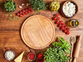Cutting wooden board with traditional pizza preparation ingridients: mozzarella, tomatoes sauce, basil, olive oil Royalty Free Stock Photo