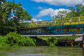 CUYABENO, ECUADOR - NOVEMBER 16, 2016: Bridge over the Cuyabeno River with a pipeline suspended beside it, Cuyabeno
