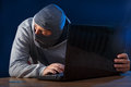 Cyber crime criminal hacking into a computer looking over his shoulder Royalty Free Stock Photo