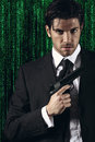 Cyber spy elegant posing with gun in hand green matrix background portrait Stock Photos
