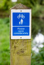 Cycle considerately information sign fitted to wooden poll at wa Royalty Free Stock Photo