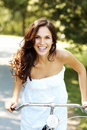 Cycling in park - Happy young woman riding a cycle Royalty Free Stock Image