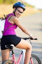 Cycling portrait of young sporty woman with bicycle outdoor Stock Image