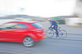 Cyclist on Alpina bike overtaking car. Royalty Free Stock Images