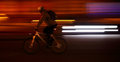 Cyclist big city background night light motion Royalty Free Stock Images