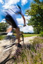 Cyclist in blurred motion riding on a rural road through green spring meadow Stock Photos