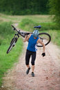 Cyclist carrying bicycle Royalty Free Stock Photography