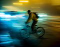 Cyclist on the city roadway in motion blur at night Stock Images