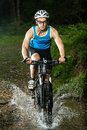 A cyclist driving through a streambed Royalty Free Stock Image