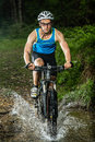 Cyclist driving through a streambed Royalty Free Stock Photos