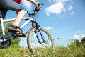 Cyclist on green grass young a mountain bike and the blue sky in the park Stock Images