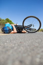 Cyclist lying on the road after an accident Royalty Free Stock Photo