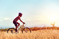 Cyclist man riding mountain bike in field horizontal view of healthy lifestyle Stock Image