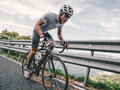 Cyclist in maximum effort a road outdoors Royalty Free Stock Photo