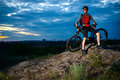 Cyclist Resting with Mountain Bike on the Rock at Sunset Royalty Free Stock Photo